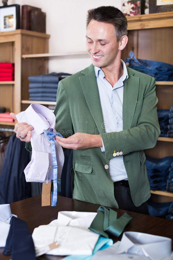 Male seller displaying diverse cloths in boutique royalty free stock images