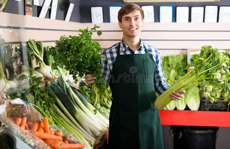 Male seller posing with celery stock image