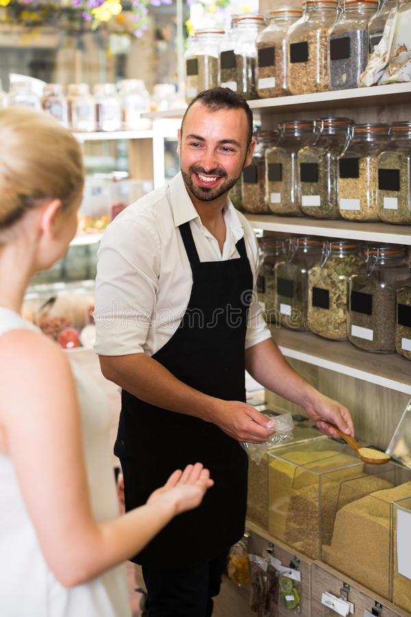 Male seller in store of ecological goods. Portrait of friendly smiling male seller selling dried herbs and cereals in store with ecological goods stock photos