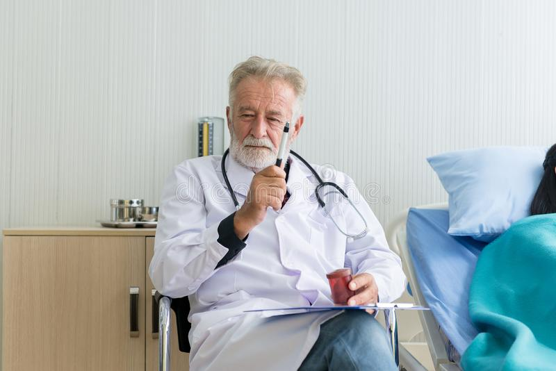 Man senior doctor analysis results and examining to asian woman patient with follow up treatment at hospital royalty free stock photography