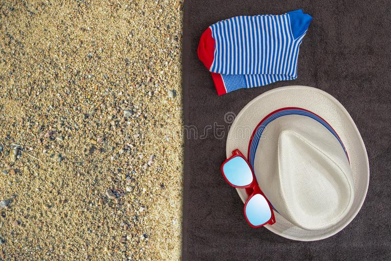 Male set of things for summer holidays hat, sunglasses, socks on a on a dark towel and yellow sand background. Top view. royalty free stock image