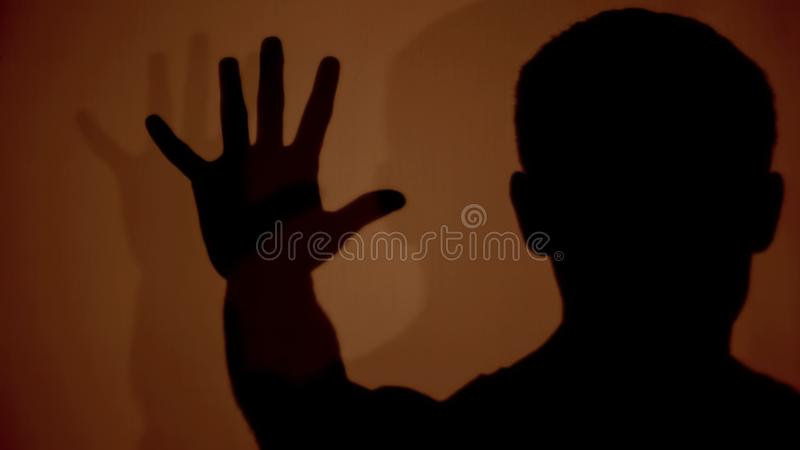 Male shadow showing stop gesture, protesting against aggression and violence. Stock photo stock photos
