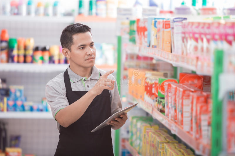 Male shopkeeper working in a grocery store. Asian male shopkeeper working in a grocery store stock photos