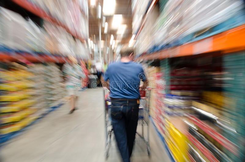 Male shopper in store with shopping cart. Male shopper in large store with shopping cart; blurred image to imply motion, action and stress royalty free stock photos