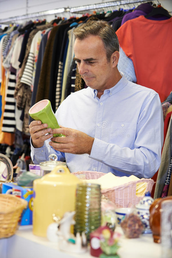 Male Shopper In Thrift Store Looking At Ornaments. Man Shopping In Thrift Store Looking At Ornaments stock photos