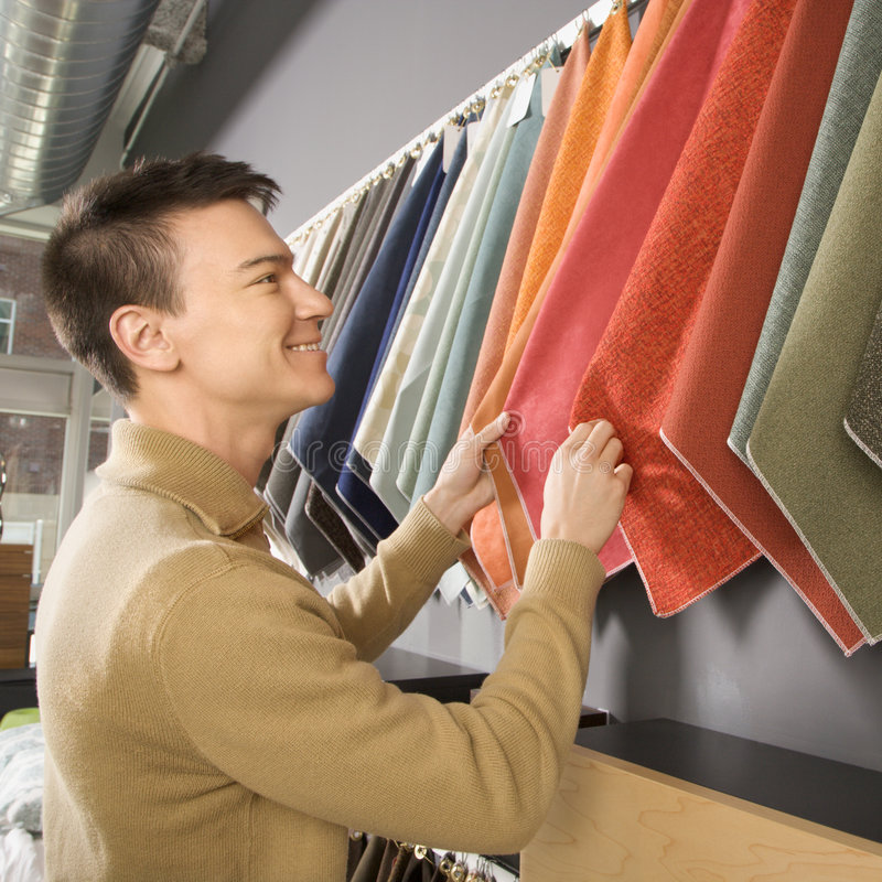 Male shopping. Asian male looking at fabric swatches in retail store stock image