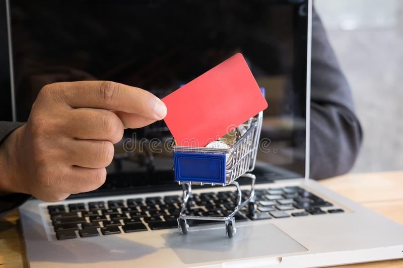 Male showing a credit card in mini supermarket cart trolley full. Young male showing a credit card in mini supermarket cart trolley full of coins on laptop stock photo