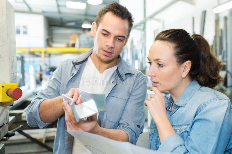 Male showing female worker industrial process in factory royalty free stock photography