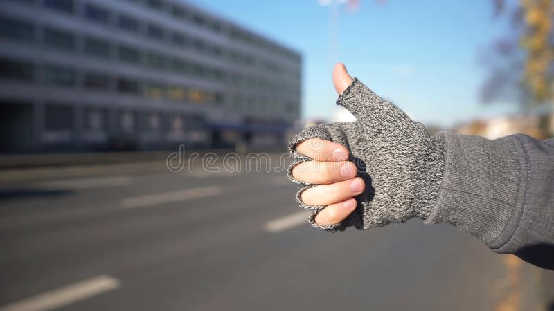 Male showing thumbs up to catch car, hitchhiking and travelling, adventure stock image