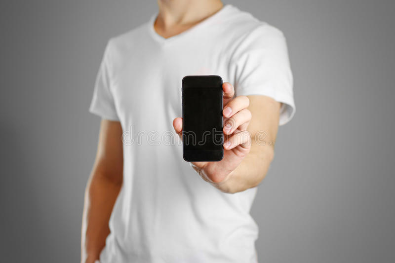 Male shows a black phone. Keeps it upright. Isolated stock photo