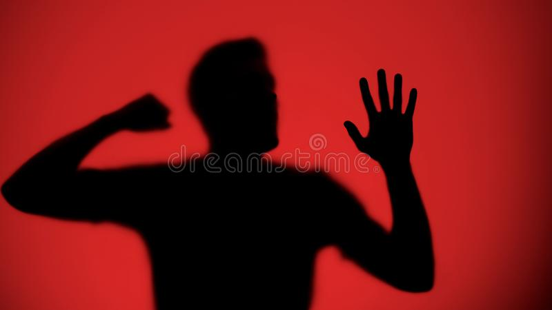 Male silhouette knocking on glass, red light background, warfare concept stock photo