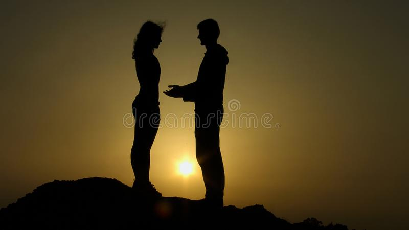 Male silhouette reaching out hands to girl, offering help, supportive friend royalty free stock photo