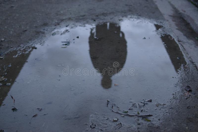 Male silhouette reflected in dark puddle cloud ominous spooky royalty free stock photos