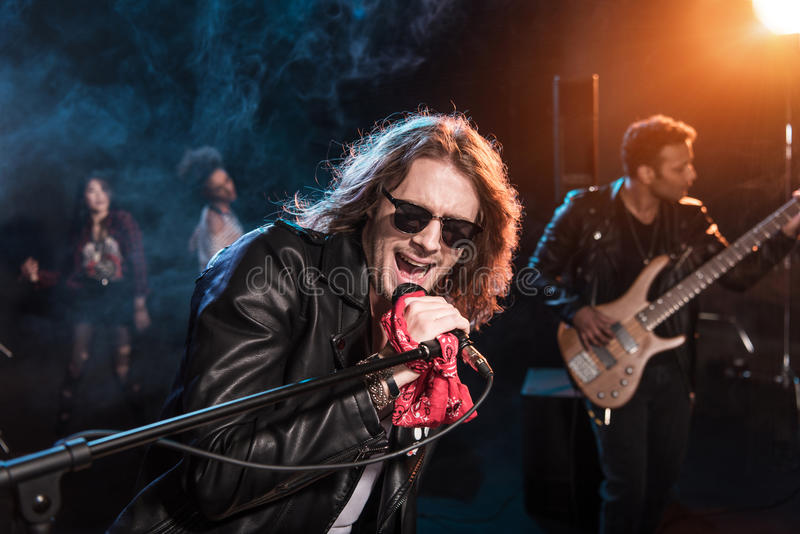 Male singer with microphone and rock and roll band performing hard rock music. On stage royalty free stock photo