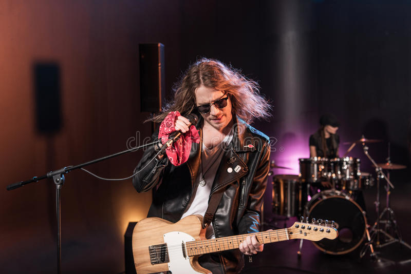 Male singer with microphone and rock and roll band performing hard rock music. On stage stock images