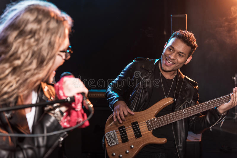 Male singer with microphone and rock and roll band performing hard rock music. On stage stock photos