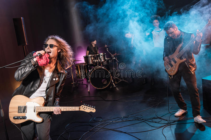 Male singer with microphone and rock and roll band performing hard rock music. On stage royalty free stock images