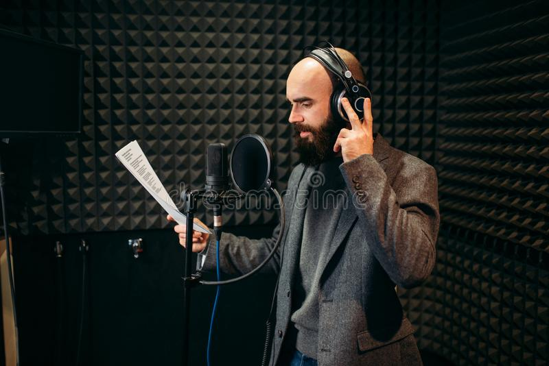 Male singer songs in audio recording studio. Male singer in headphones songs in audio recording studio. Musician listens composition, professional music stock photo
