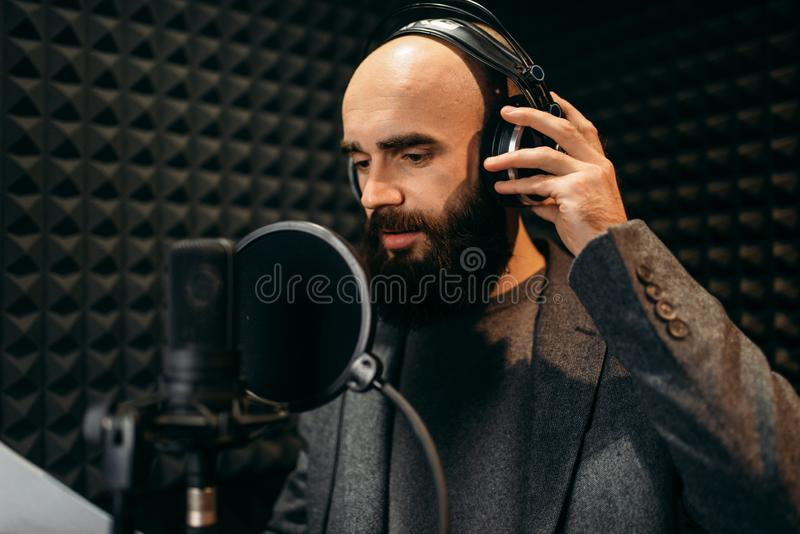 Male singer songs in audio recording studio. Male singer in headphones songs in audio recording studio. Musician listens composition, professional music royalty free stock photos