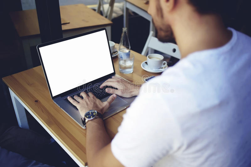 male sitting in front open laptop computer with blank copy space screen for your text message or advertising content stock photography