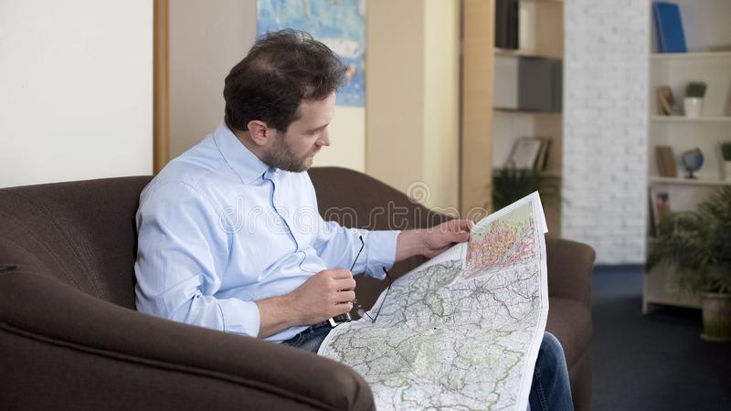 Male sitting on sofa and looking at map, choosing destination for vacation royalty free stock photo