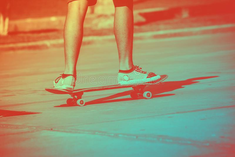 Male skateboarder on a skateboard is riding at sunset stock photography