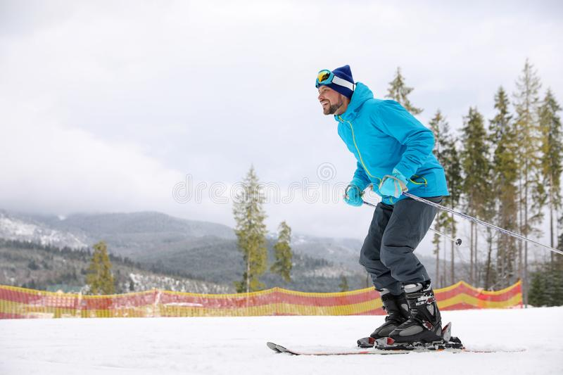 Male skier on slope at resort, space for text. Winter. Vacation royalty free stock images