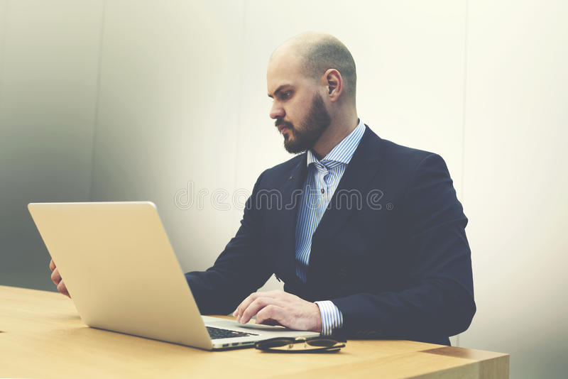 Male skilled employer is reading on portable net-book resume before interview with specialists. Young serious man investor is examining on laptop computer royalty free stock photography