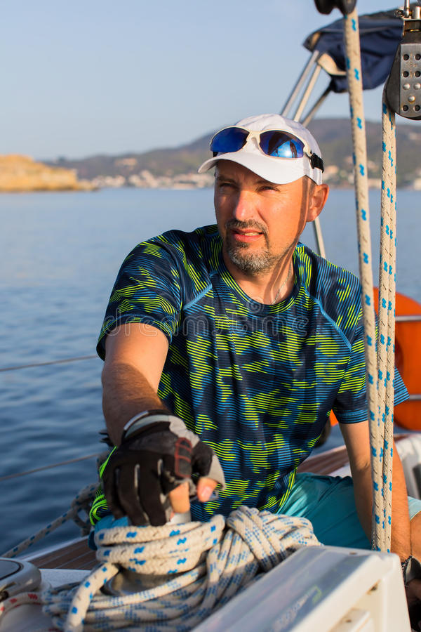 Male skipper on his yacht sailing boat. Sport. stock photos