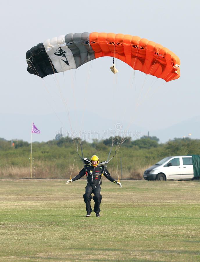 Male skydiver making safe landing landing on grass with open bright colourful parachute. royalty free stock photo