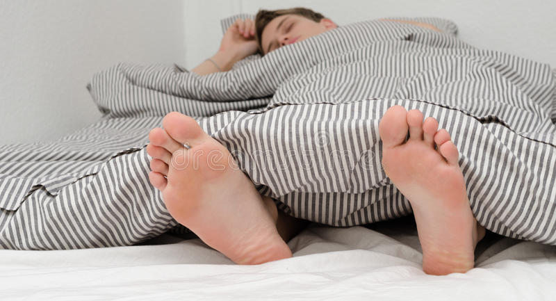 Male sleeping. In a bed, feet sticking out from covered stock photography