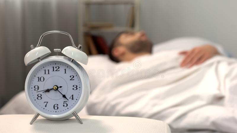 Male sleeping in bed, white alarm clock standing on table morning, biorhythm. Stock photo stock photos