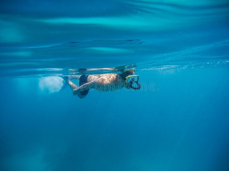 Young man swimming and snorkeling with mask and fins in clear blue water. Male snorkeling in the sea leaving trail of bubbles behind him stock photos