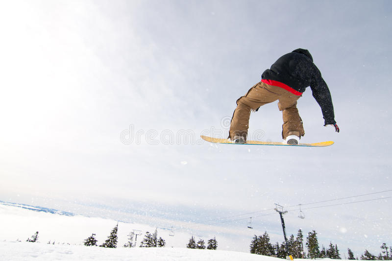 Male Snowboarder Catches Big Air. Male Snowboarder Catches Big Air on a Bright Sunny Day stock photos