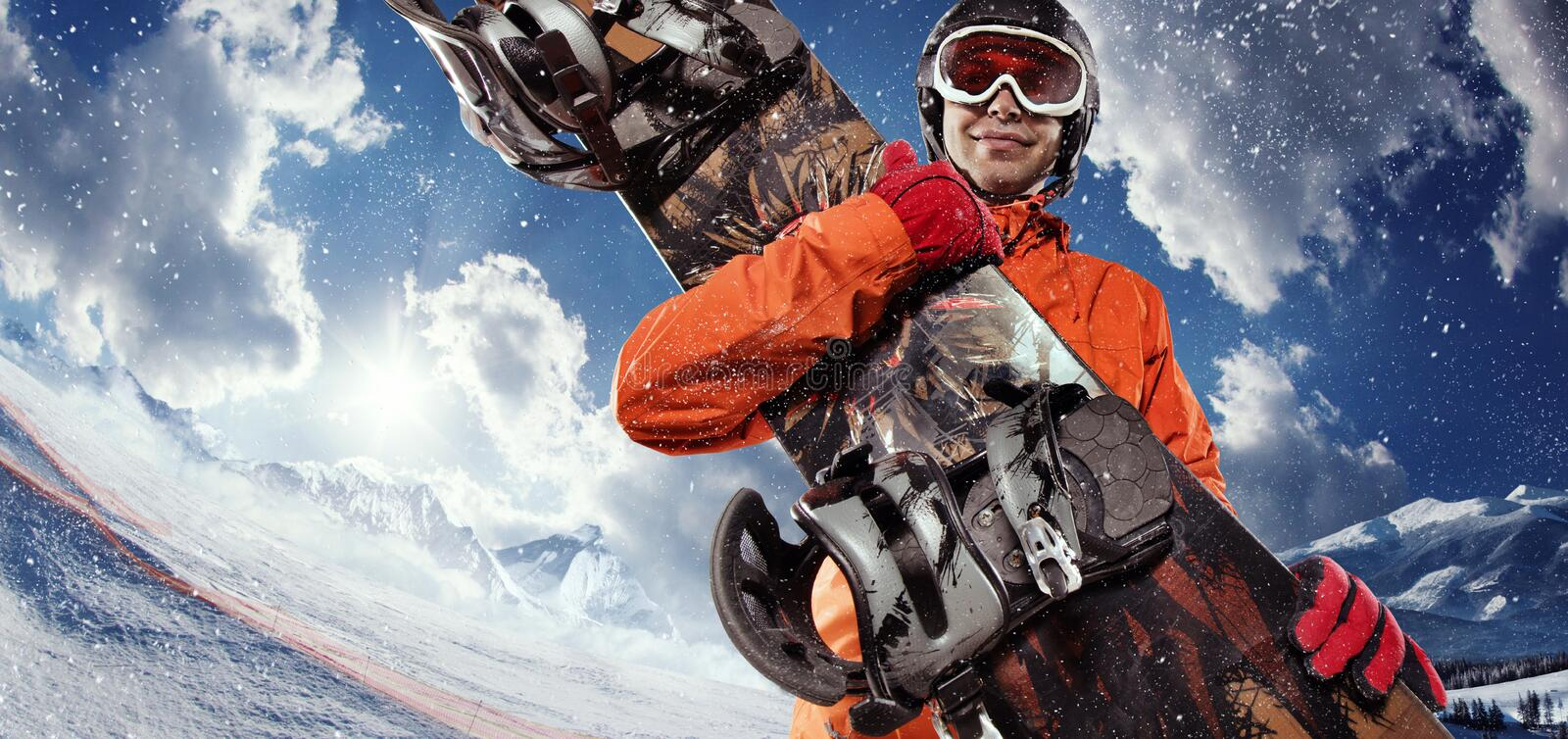 Snowboarder holding his snowboard. A male snowboarder holding his snowboard on a blue sky and snow background stock photos