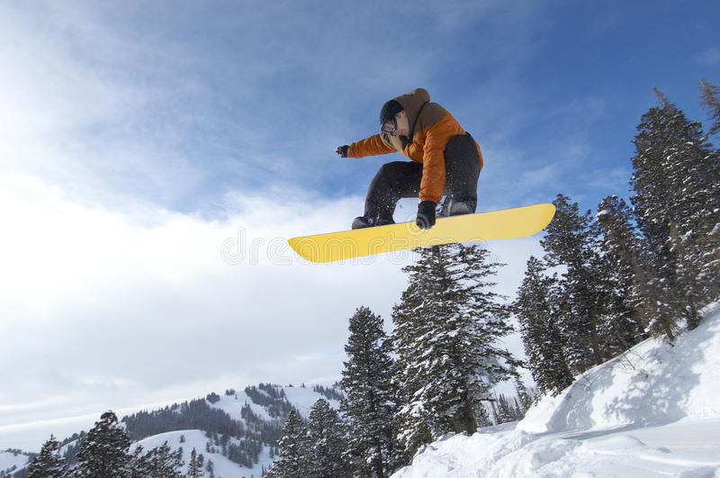 Male Snowboarder Jumping Over Snow Covered Hill stock image