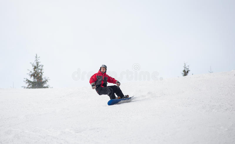 Male snowboarder riding down from the mountain in winter day. Young man snowboarder riding over the slope at the mountains overlooking a ski run on the snowy stock photography