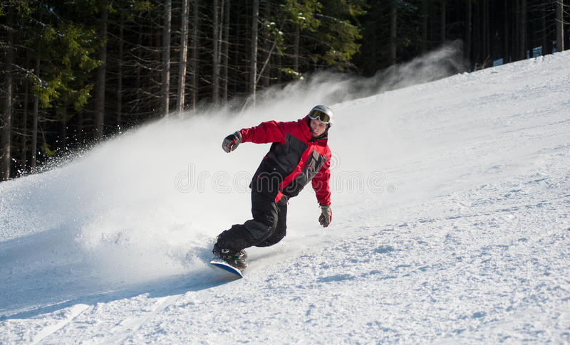 Male snowboarder slides down from the mountain. Man snowboarder slides down from the mountain in winter day, overlooking the snowy slope at a winter resort royalty free stock photography