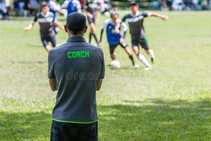 Male soccer or football coach standing on the sideline watching royalty free stock images
