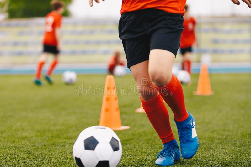 Male soccer player - slalom drills training. Football practice session. Soccer players kicking ball on pitch. Football stadium in the background royalty free stock photo