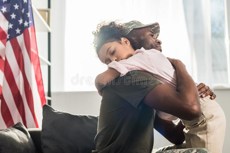 Male soldier in camouflage clothes and her daughter embracing. On sofa stock photos
