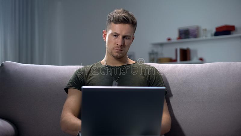 Male soldier typing on laptop pc at home, communication concept, military app. Stock photo royalty free stock photo