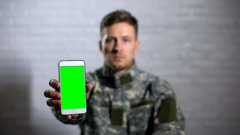 Male soldier in uniform showing smartphone with green screen at camera, app. Stock photo royalty free stock photography