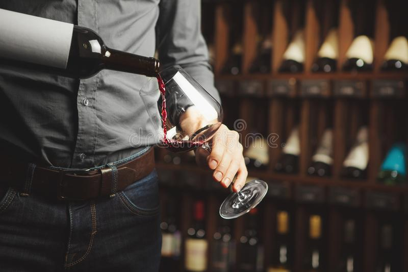 Male sommelier pouring red wine into long-stemmed wineglasses, close-up shot. Waiter with bottle of alcohol beverage. stock images