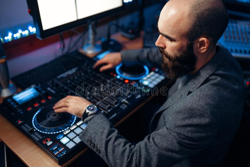 Male sound editor in the recording studio. Male sound editor at remote control panel in the recording studio. Musician at the mixer, professional audio mixing royalty free stock photos
