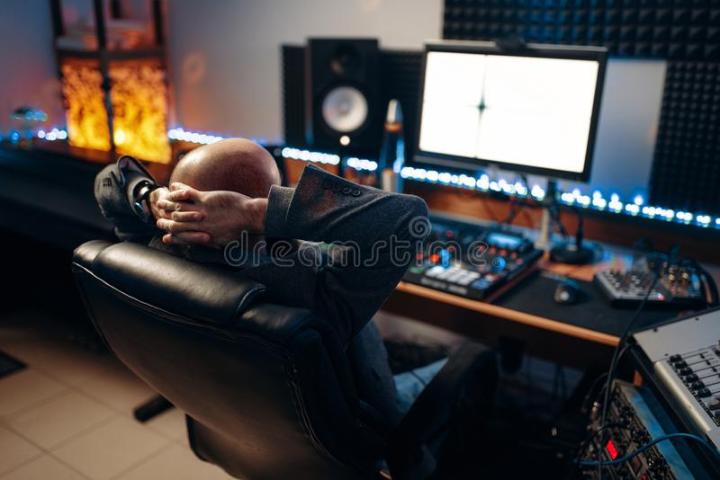 Male sound engineer at remote control, back view. Male sound engineer at remote control panel, back view, recording studio. Musician at the mixer, professional stock image