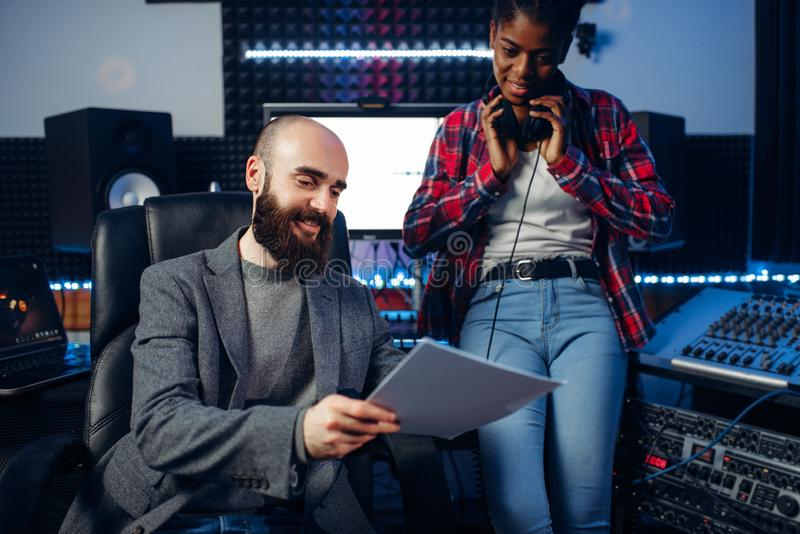 Male sound producer and female singer in studio. Male sound producer and female singer in headphones listens composition in recording studio. Professional audio stock photo