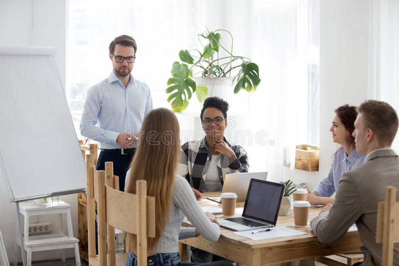Male speaker give flipchart presentation to diverse workers stock photo