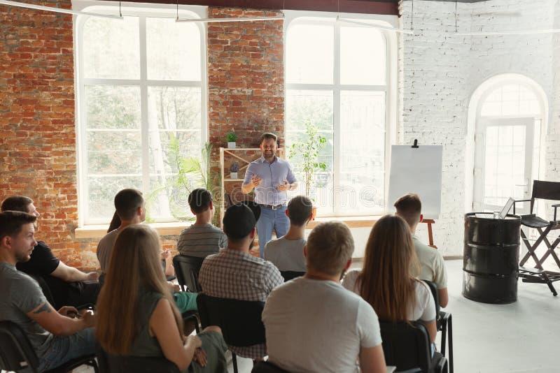 Male speaker giving presentation in hall at university workshop royalty free stock image