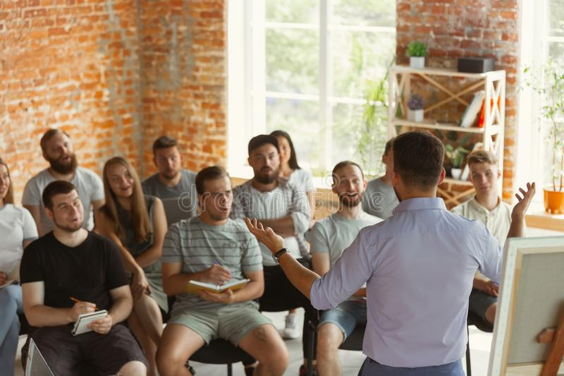 Male speaker giving presentation in hall at university workshop stock photography